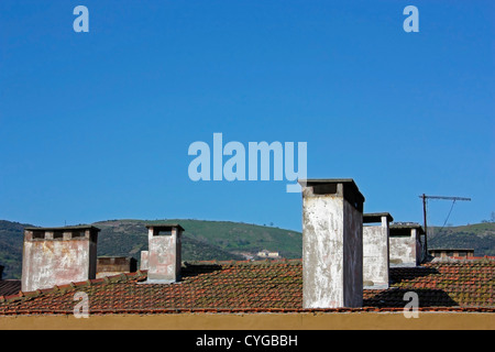 Chimneys on roof with blue sky and hills - Stock Photo