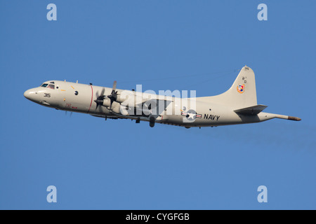 United States Navy Lockheed P-3C Orion turboprop maritime patrol plane flying against a clear blue sky - Stock Photo