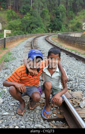 Sri Lankan boys on Nine Archrailway  bridge at Demorada in the Sri Lankan highlands. - Stock Photo