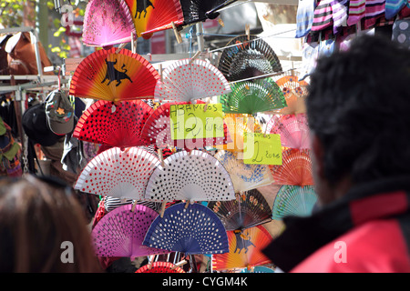 People tourists browsing Spanish flamenco style fans for sale, market stall, El Rastro, Madrid, Spain - Stock Photo