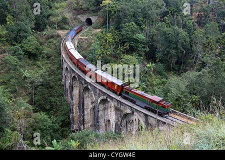 Commuter passenger train passing over Nine Arch bridge at Demorada in the Sri Lankan highlands. - Stock Photo