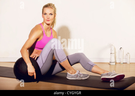 Fitness instructor at the gym sitting on the floor with a pilates ball - Stock Photo