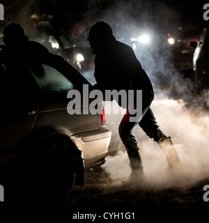 Cars stuck in a muddy field on a cold night following a firework display - Stock Photo