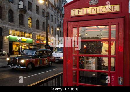 Red telephone box and black cab on April 10, 2007 in London. - Stock Photo