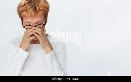 a tired woman is rubbing her eyes behind her glasses. High key and copy-space. - Stock Photo