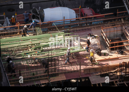 Highrise Construction Site with tradesmen, NYC - Stock Photo