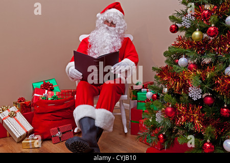 Santa Claus sat in a rocking chair reading the 'naughty or nice' list surrounded by gift wrapped presents. - Stock Photo