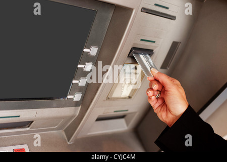 Cropped view of a female hand inserting a bank card into an ATM to begin a financial transaction - Stock Photo
