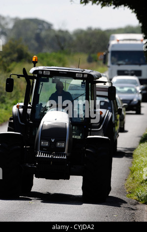 Traffic stuck behind a tractor on a road in Gloucestershire UK - Stock Photo