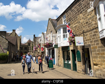 people shopping and walking around the Derbyshire village of Bakewell in the Peak District England - Stock Photo