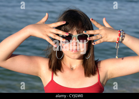 girl shows her painted nails in front of face - Stock Photo