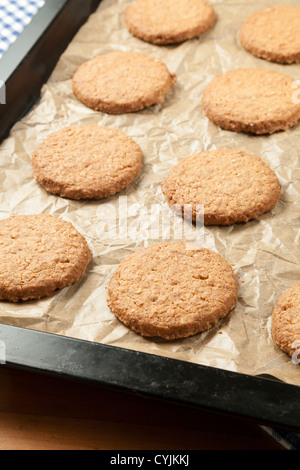 Oat biscuits on baking sheet freshly baked - Stock Photo