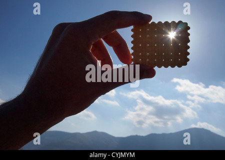 Sun is shining through one of the holes in a biscuit held towards the sun - Stock Photo