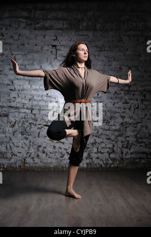 Full-length portrait of young beautiful woman doing yoga excercise against a brick wall - Stock Photo