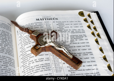 An open bible with a cross lying on a page