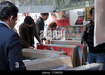 Shoppers browsers flick through posters reproduction art works, flea market El Rastro Madrid, Spain - Stock Photo