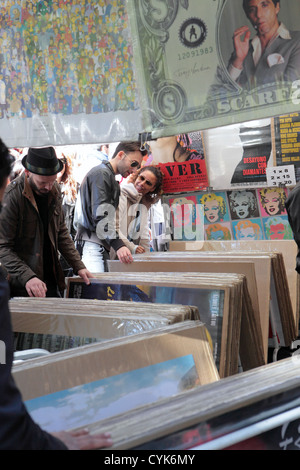 Shoppers young couple browsers flick through posters reproduction art works, flea market El Rastro Madrid, Spain - Stock Photo