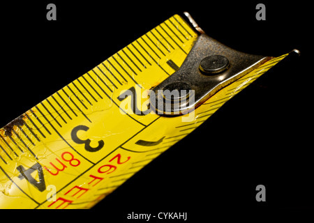 Close up of a worn used old builders measuring tape on black. - Stock Photo