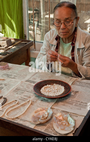 Myanmar, Burma. Burmese Woman Threading Pearls onto Necklace, Inle Lake, Shan State. - Stock Photo