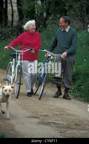 active senior couple out on bikes - Stock Photo