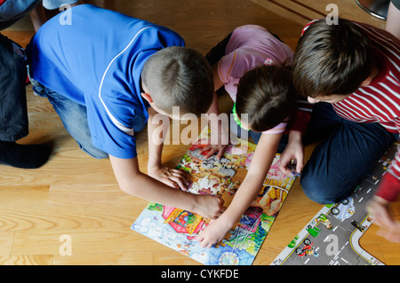 Four children doing a jigsaw puzzle - Stock Photo