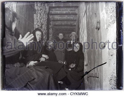 people sitting in a corridor of tenant housing 1900s - Stock Photo