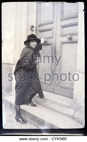 young adult woman by front door early 1900s - Stock Photo