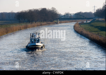 Icebreaker in Dutch canal breaks the ice in pieces - Stock Photo