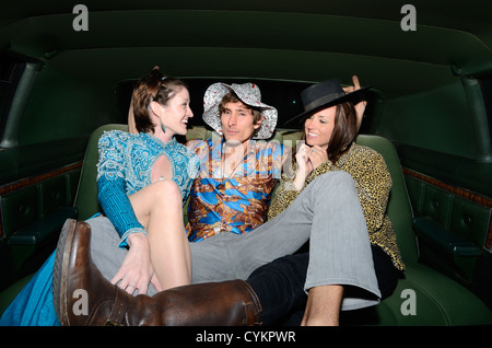 Man sitting with women in limousine - Stock Photo