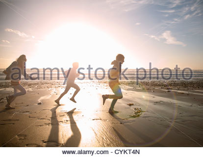 Family running together on beach - Stock Photo