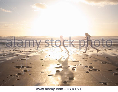 Mother and son running on beach - Stock Photo