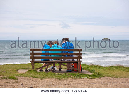 Mother and sons on bench at beach - Stock Photo