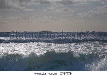 Rocky waves crashing on beach - Stock Photo