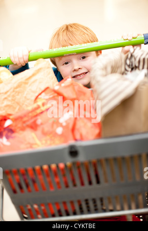 Boy pushing cart in grocery store - Stock Photo