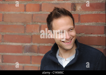Smiling man leaning against brick wall - Stock Photo