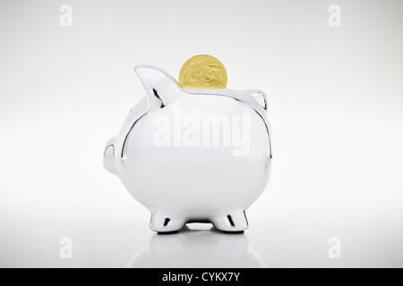 Gold coin dropping into piggy bank - Stock Photo
