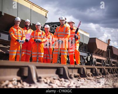 Railway workers standing on train tracks - Stock Photo
