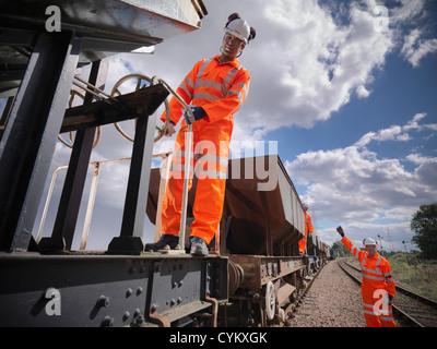 Railway workers standing on train - Stock Photo