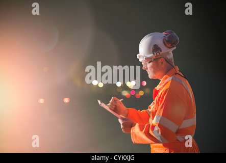 Railway worker writing on clipboard - Stock Photo