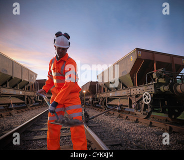 Railway worker shoveling on train tracks - Stock Photo