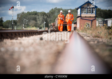 Railway workers walking on train tracks - Stock Photo