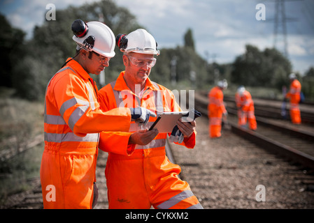 Railway workers using tablet computer - Stock Photo