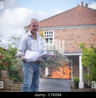 Man burning papers in garbage can - Stock Photo