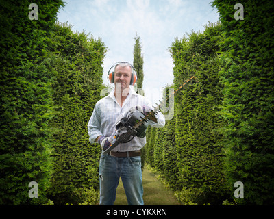 Man holding hedge trimmer in garden - Stock Photo