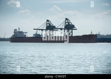 Silhouette of container ship and cranes - Stock Photo