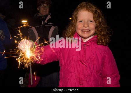 6 year old girl having fun with sparklers at firework display, Chiddingfold, Surrey, UK. November, 2012. - Stock Photo