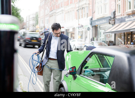 Man charging electric car on street - Stock Photo