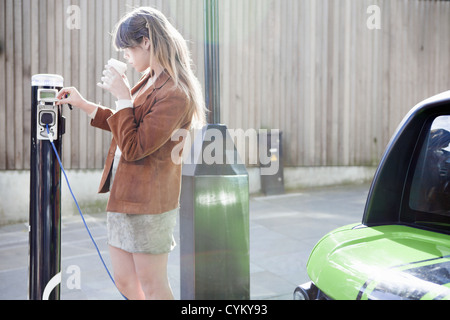 Woman charging electric car on street - Stock Photo