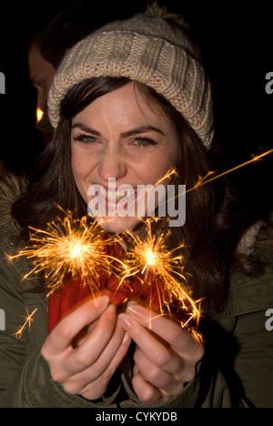 26 year old girl having fun with sparklers on bonfire night, Chiddingfold, Surrey, UK. November 2012. - Stock Photo