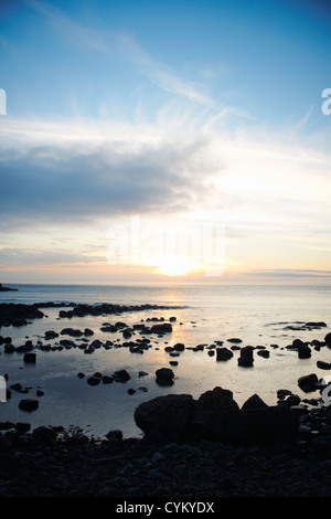 Water washing up on rocky beach - Stock Photo